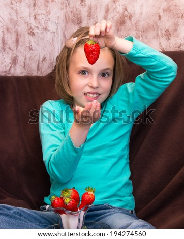 Little girl eating ripe strawberries with sugar - stock photo