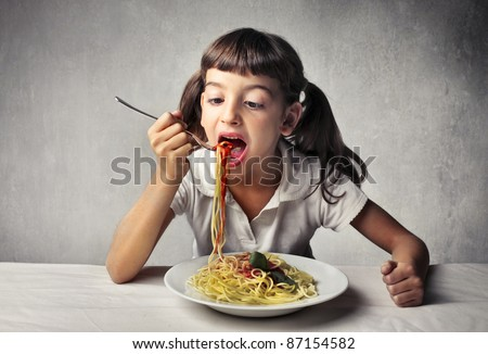 Little girl eating spaghetti - stock photo
