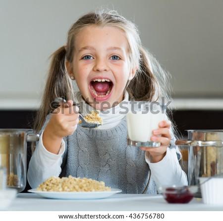 Little girl eating tasty porridge at kitchen table indoors - stock photo