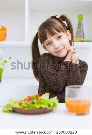 Little girl eating vegetable salad - stock photo
