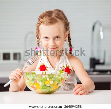 Little girl eating vegetable salad in the kitchen. Child at home