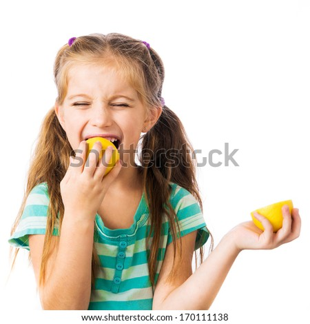 little girl eats a lemon isolated on a white background - stock photo
