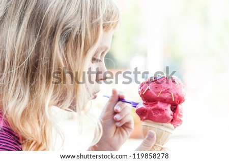 Little girl eats big ice-cream in the park. Profile portrait with selective focus - stock photo