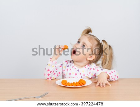little girl eats carrot with fork.Sitting at the table - stock photo