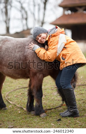 Little girl embracing her best friend pony at countryside outdoors - stock photo