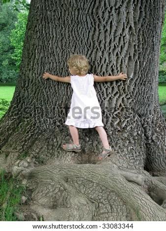 Little Girl embracing Huge Tree - stock photo
