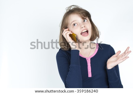 Little girl emotional talking on mobile phone. Studio photography on a light gray background. Age of child 10 years. - stock photo