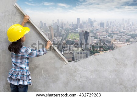 Little girl engineering ideas concept with hand holding plastering tools renovating a house. With painting modern city skyline, cityscape, building, skyscraper on wall