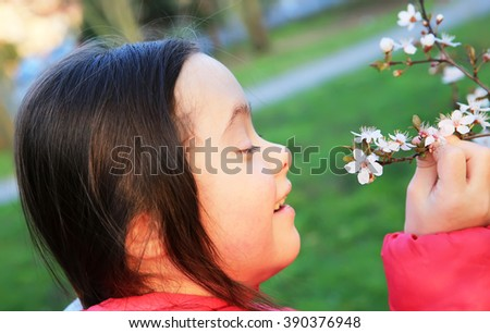 Little girl enjoy with the spring flowers branch - stock photo