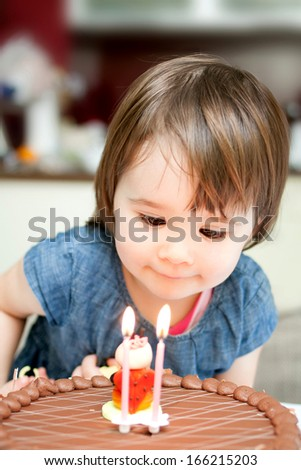 Little girl enjoying her birthday cake.