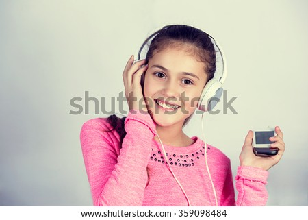 Little girl enjoying music in headphones with a mobile phone at home relaxing. Relaxed little girl listening to music with earphones  looking serene and happy. - stock photo