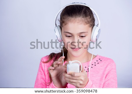 Little girl enjoying music in headphoneswith a mobile phone at home relaxing. Relaxed little girl listening to music with earphones  looking serene and happy. - stock photo