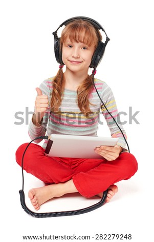 Little girl enjoying music listening in headphones attached to her tablet computer, gesturing thumb up, overw white background - stock photo