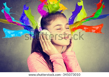 Little girl enjoying music with splash colors from headphones at home relaxing. Relaxed little girl listening to music with earphones with eyes closed looking serene and happy. - stock photo