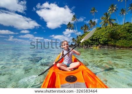 Little girl enjoying paddling in colorful orange kayak at tropical ocean water during summer vacation - stock photo