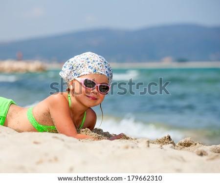 Little girl enjoying summer day on a beach - stock photo