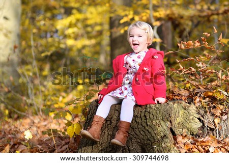 Little girl enjoying sunny day in autumn park. Child hiking in the forest and playing with golden leaves. Happy kid sitting on a stump. - stock photo