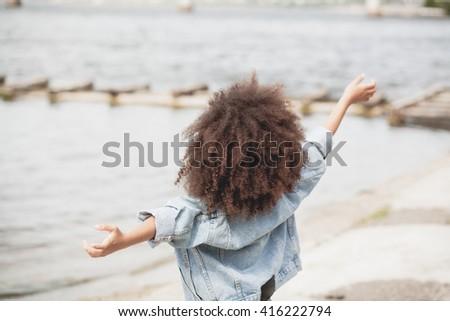 Little girl enjoying with freedom near the sea - stock photo