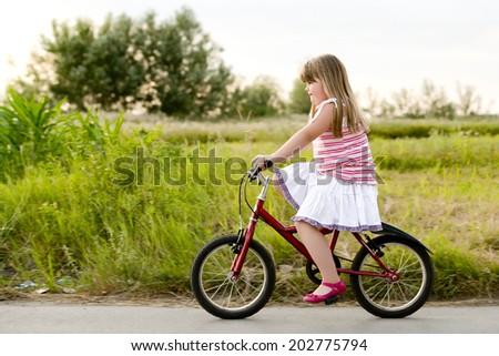 little girl enjoys riding a bike/little girl enjoys riding a bike - stock photo