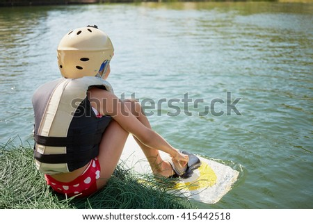 Little girl equipped for wakeboard sporting sits near water, rear view.