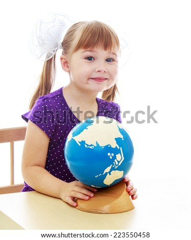 Little girl examines the globe sitting at the table. Happy childhood, fashion, autumnal mood concept. Isolated on white background