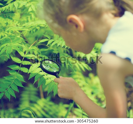 Little girl examining nature through the magnifying glass. - stock photo