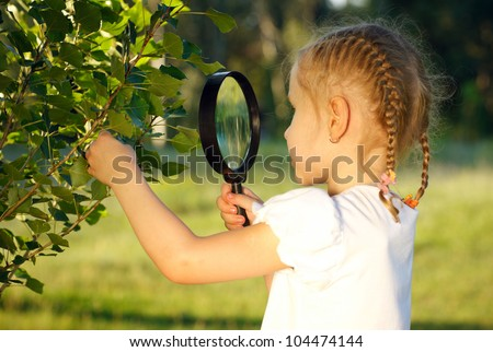 Little girl examining the tree leaves through the magnifying glass outdoors - stock photo