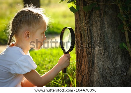 Little girl examining the tree stem through the magnifying glass outdoors - stock photo