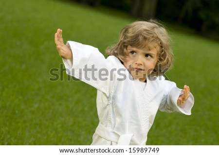 Little girl exercising in the garden - stock photo
