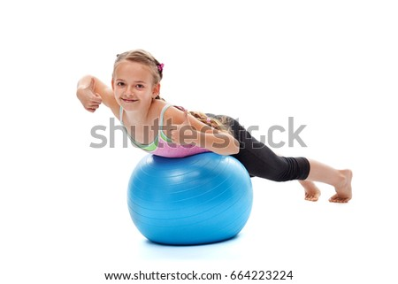 Little girl exercising on a large gymnastic ball and enjoying physical effort - showing thumbs up, isolated