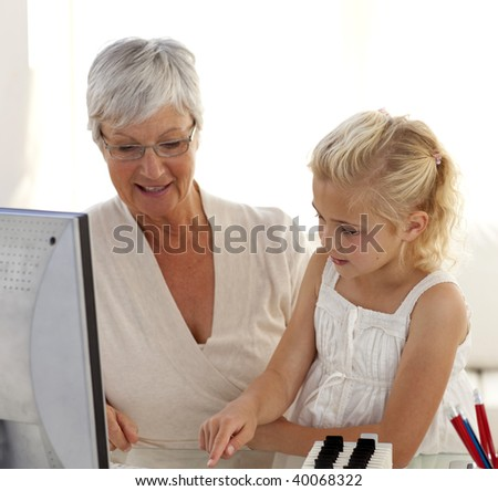 Little girl explaining her grandmother how to use a computer at home