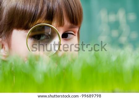 Little girl exploring the grass - stock photo