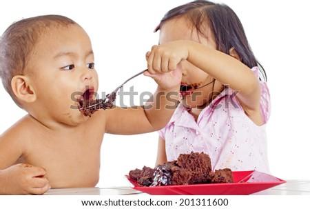 Little girl feeding a little boy with a cake. - stock photo