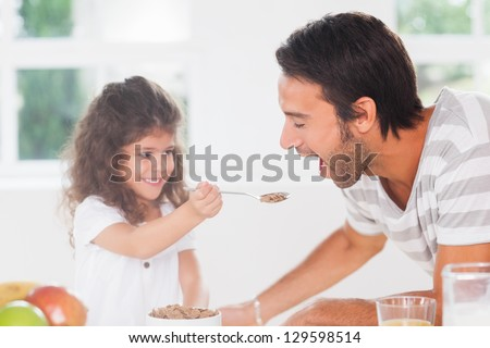Little girl feeding cereal to father in kitchen