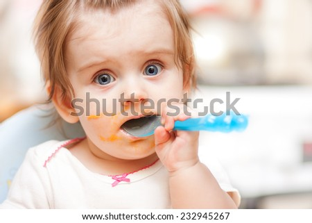 little girl feeding from a spoon on blue chair