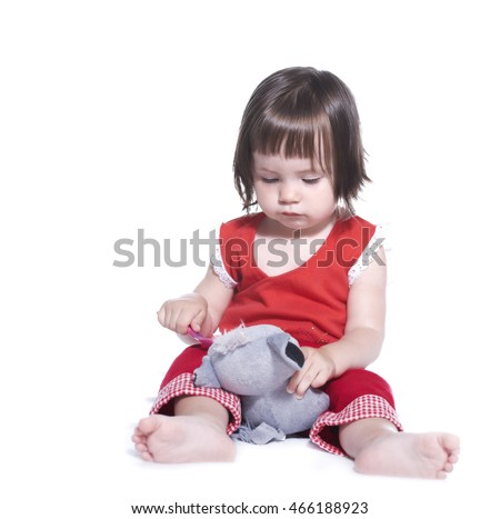 Little girl feeding spoon plush toy. Isolated on white background