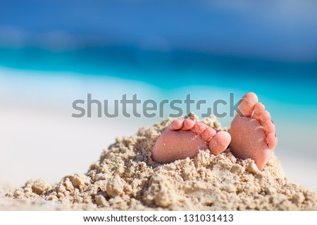 Little girl feet covered with tropical sand