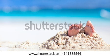 Little girl feet covered with tropical sand - stock photo