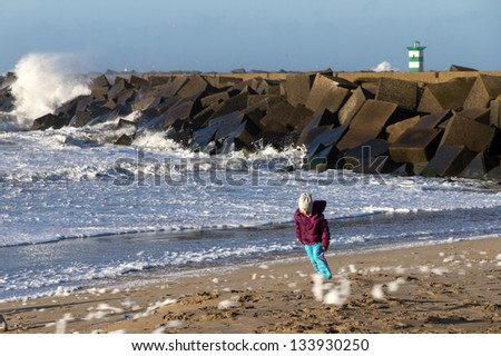 Little girl fighting against the wind on a stormy november day on the beach near Scheveningen in the Netherlands - stock photo
