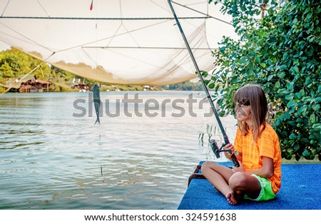 Little girl fishing on the river Bojana in Montenegro