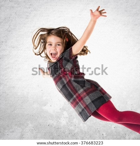 Little girl flying over textured background