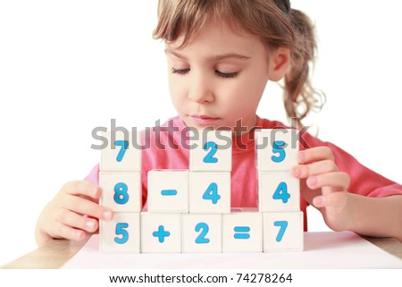 Little girl folds equalizations from cube - stock photo