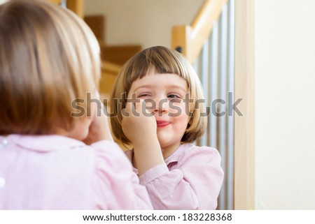 little girl front of  mirror with cosmetic - stock photo