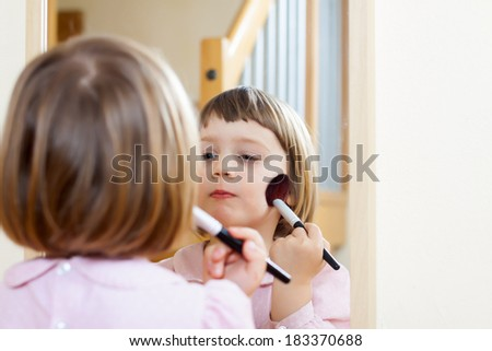 little girl front of  mirror with cosmetic  brush - stock photo