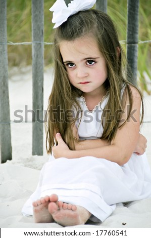 Little girl frowning sitting on the beach by a wooden fence dressed in a white dress with a big bow in her brunette hair. - stock photo