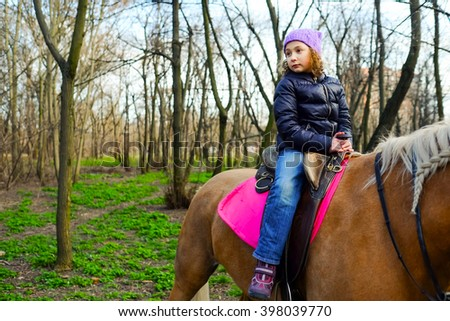 Little girl galloping on horse. Cute girl on a pony in the park on a sunny summer day on the nature. Horseback riding, lovely equestrian, child, kid is riding a horse. - stock photo