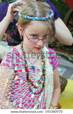 Little girl gets her hair fixed at a festival - stock photo