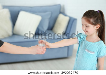 Little girl getting glass of water in living room - stock photo