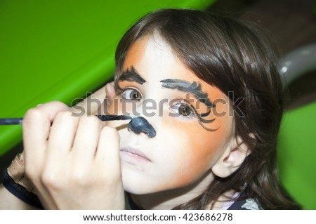 Little girl getting her face painted like a tiger by face painting artist