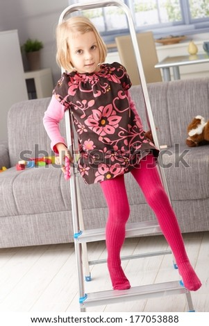 Little girl getting off ladder at home in living room. - stock photo